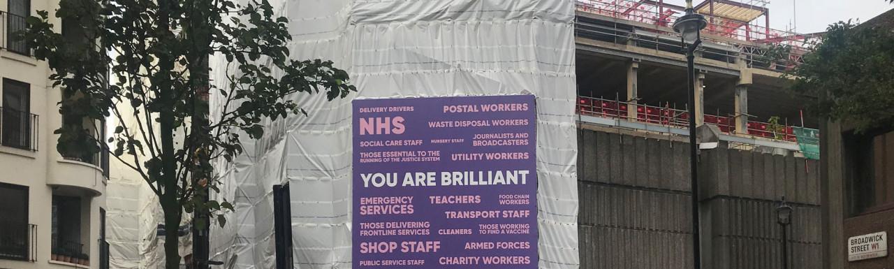 72 Broadwick Street development under construction. NHS - you are brilliant banner.