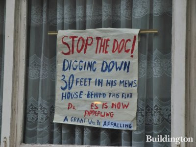 Berrington House resident frustrated by construction work behind Berrington House. The sign says: 'Stop the Doc! Digging down 30 feet in his mews house behind this flat. Dr. ... is now appealing a grant will be appalling.'